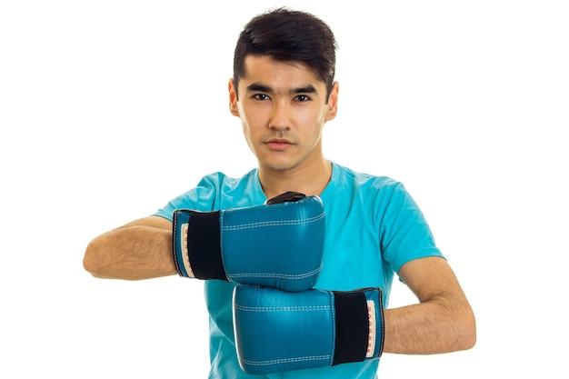 Jonge man poseren in blauw shirt en bokshandschoenen geïsoleerd op een witte achtergrond in studio