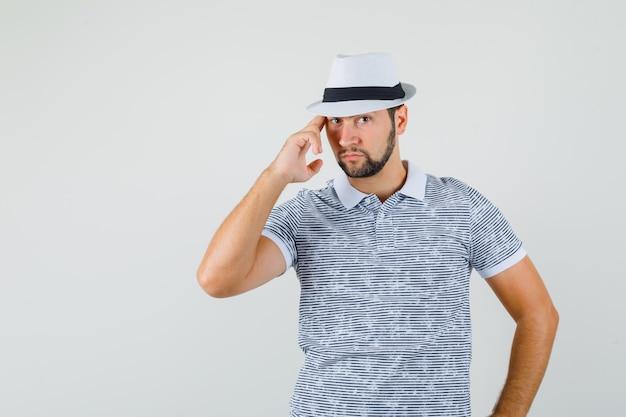 Jonge man poseren in gestreept t-shirt, hoed en op zoek macho, vooraanzicht.
