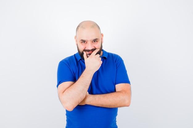 Jonge man poseren met de hand op zijn lippen, glimlachend in blauw shirt vooraanzicht.
