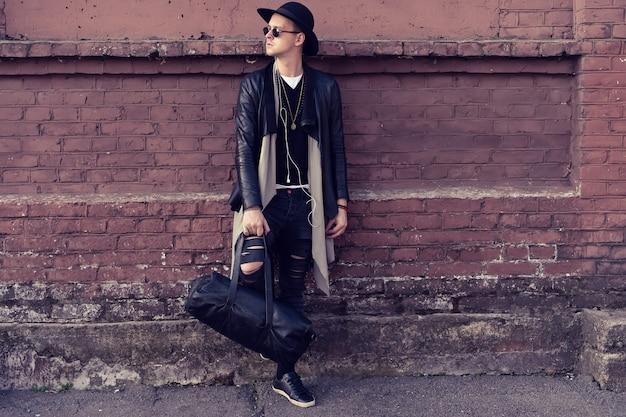 Jonge man poseren met een trendy outfit tegen een stedelijke achtergrond