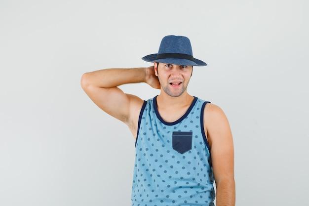 Jonge man poseren met hand op nek in blauw hemd, hoed en op zoek vrolijk. vooraanzicht.