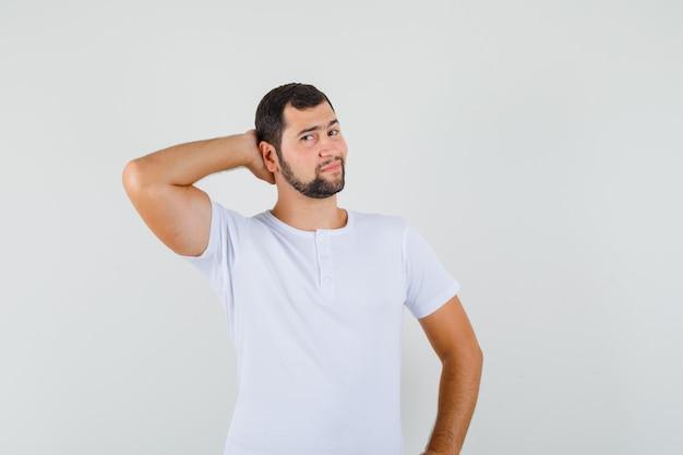 Jonge man poseren met hand op nek in wit t-shirt en ziet er indrukwekkend uit. vooraanzicht.