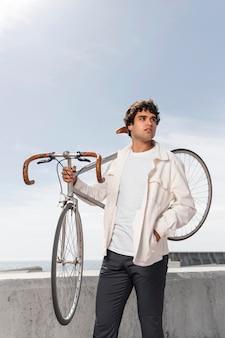 Jonge man poseren naast zijn fiets