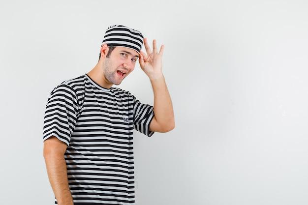 Jonge man poseren terwijl je in een t-shirt, hoed en er knap uitziet. vooraanzicht.