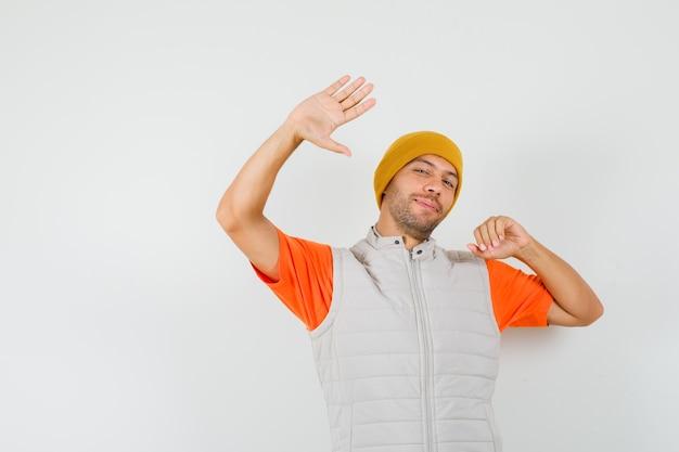 Jonge man poseren terwijl zwaaien hand in t-shirt, jasje, hoed en er mooi uit.