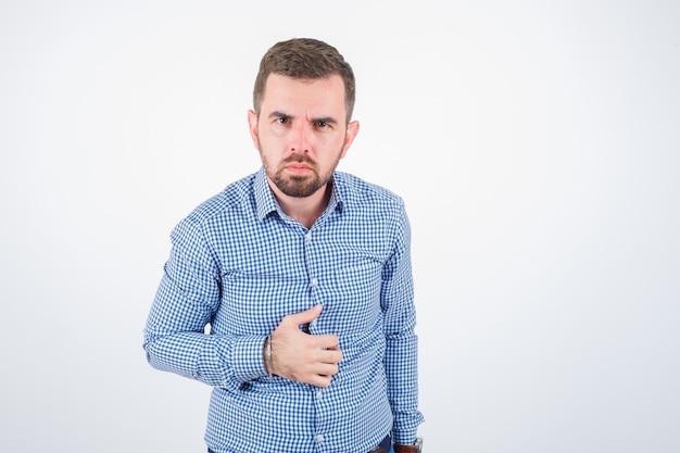 Jonge man poseren tijdens het kijken naar de camera in hemd en op zoek naar ernstige, vooraanzicht.