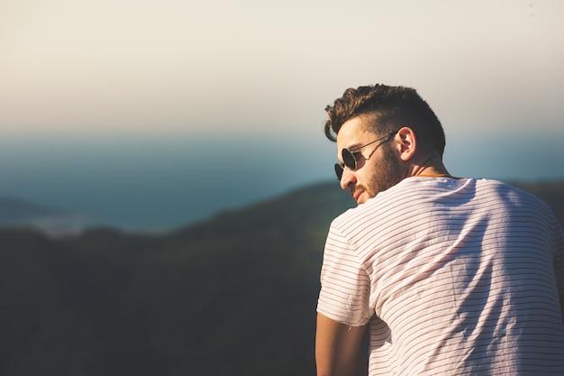 Jonge man poseren voor een foto in de bergen.