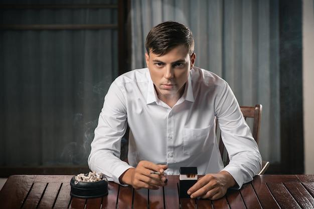 Jonge man poseren zittend aan een tafel waarop een asbak vol sigaretten staat