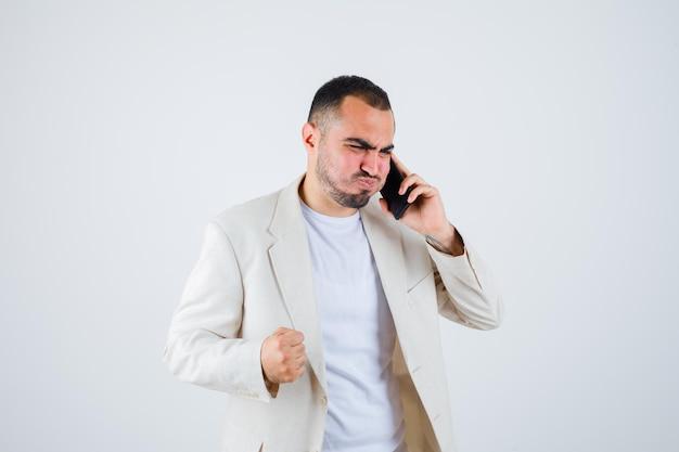 Jonge man praat met de telefoon, balt zijn vuist in wit t-shirt, jasje en kijkt gehaast. vooraanzicht.
