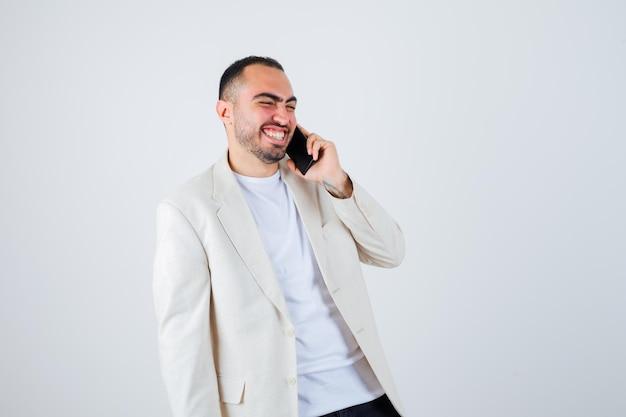 Jonge man praat met de telefoon in wit t-shirt, jas en ziet er gelukkig uit. vooraanzicht.