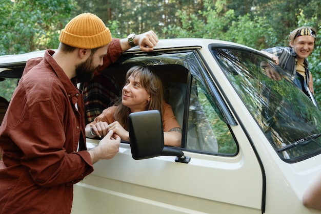 Jonge man praat met vrouw die in de auto zit en de weg vraagt