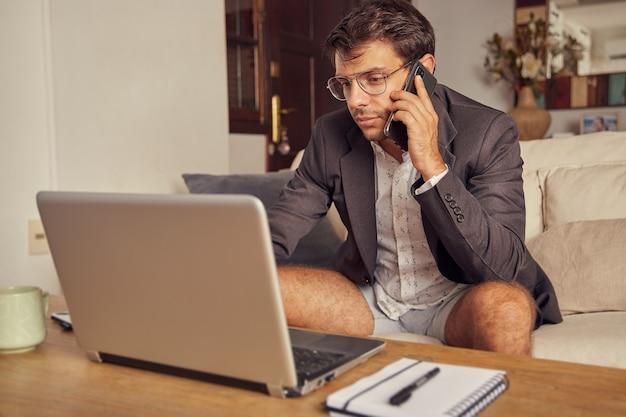 Jonge man praat op zijn mobiele telefoon en werkt op zijn laptop vanaf de bank thuis in een pak en korte broek. blauw jasje en wit overhemd. hij draagt een bril.