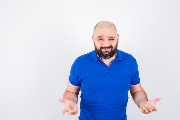 Jonge man praat terwijl hij handgebaren in een blauw shirt laat zien en er zelfverzekerd uitziet. vooraanzicht.