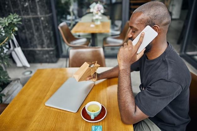 Jonge man praten aan de telefoon en kijken naar de cadeautas in zijn hand. kopje koffie pinpas en een moderne laptop op tafel