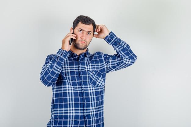 Jonge man praten aan de telefoon met hand op hoofd in ingecheckte shirt en peinzend op zoek. vooraanzicht.