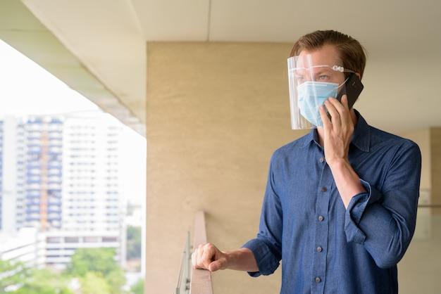 Jonge man praten aan de telefoon met masker en gelaatsscherm met uitzicht op de stad