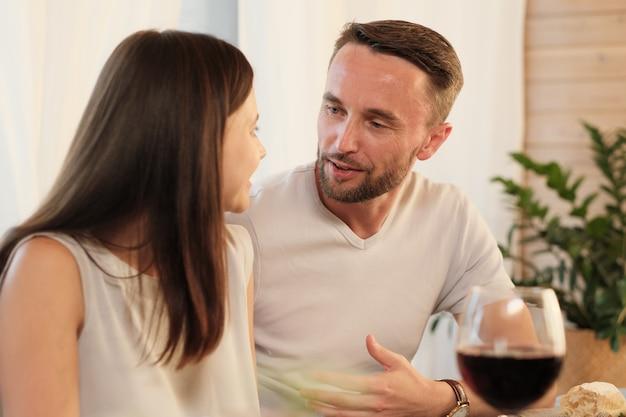 Jonge man praten met zijn vrouw aan tafel tijdens het diner