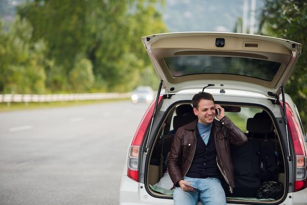 Jonge man praten mobiele telefoon en zittend op een auto kofferbak