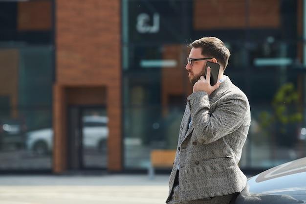Jonge man praten op een mobiele telefoon terwijl hij buiten in de stad staat