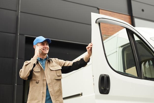 Jonge man praten op een mobiele telefoon tijdens het verzenden van dozen in de auto buitenshuis