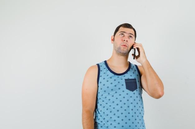 Jonge man praten op mobiele telefoon in blauw hemd en peinzend, vooraanzicht kijken.