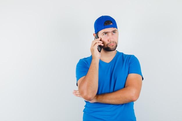 Jonge man praten op mobiele telefoon in blauw t-shirt en pet en op zoek naar serieus