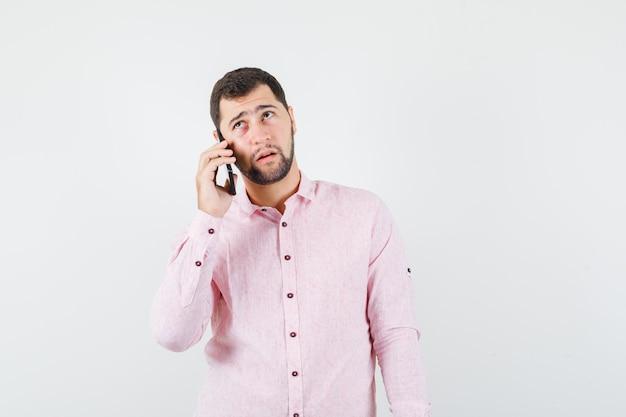 Jonge man praten op mobiele telefoon in roze shirt en peinzend kijken