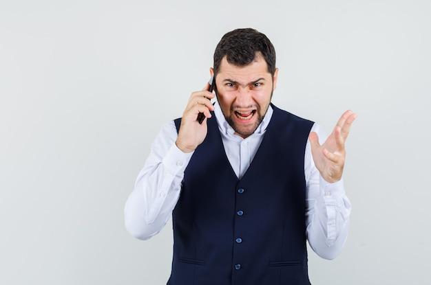 Jonge man praten op mobiele telefoon in shirt en vest en nerveus op zoek