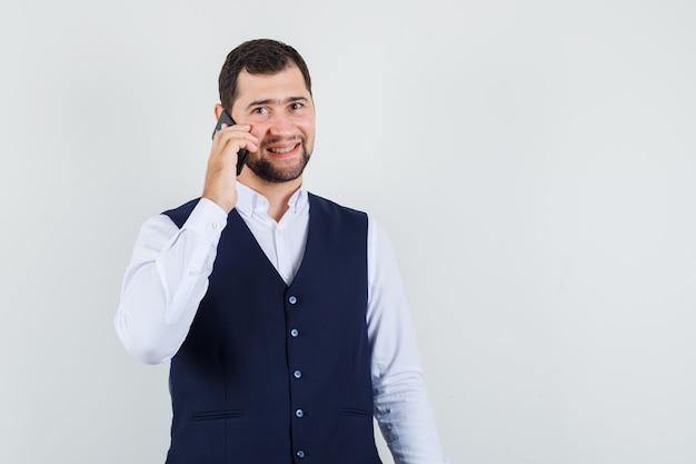Jonge man praten op mobiele telefoon in shirt en vest en vrolijk kijken