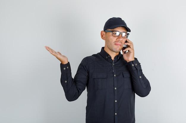 Jonge man praten op mobiele telefoon in zwart shirt met pet, bril