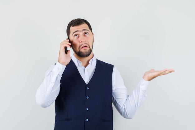 Jonge man praten op mobiele telefoon met gespreide palm in hemd en vest en hulpeloos op zoek