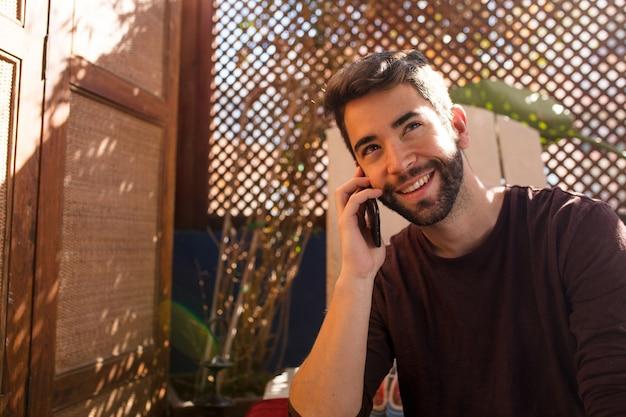 Jonge man praten op mobiele telefoon