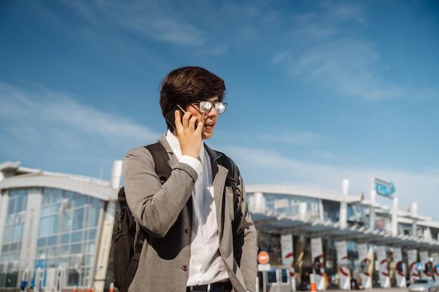 Jonge man praten op smartphone buitenshuis. communicatie concept. vooraanzicht.