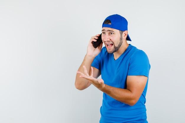 Jonge man praten over de mobiele telefoon in blauw t-shirt en pet en op zoek opgewonden