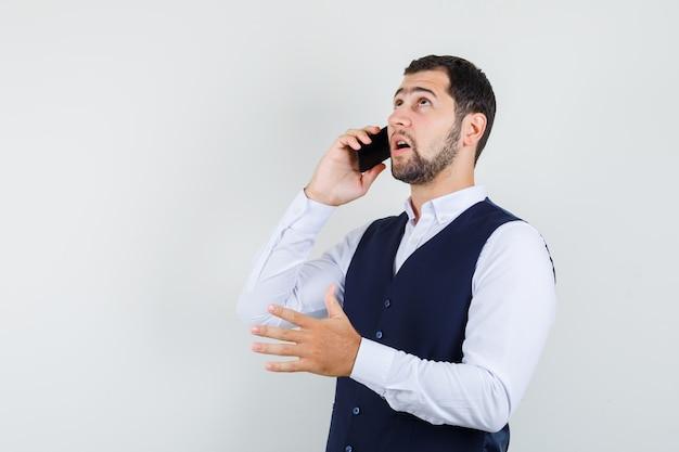 Jonge man praten over de mobiele telefoon in shirt en vest en peinzend op zoek