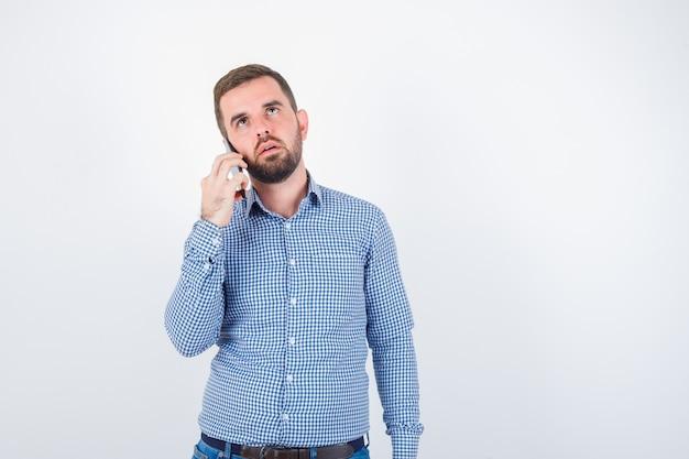 Jonge man praten over de mobiele telefoon in shirt, spijkerbroek en op zoek attent. vooraanzicht.