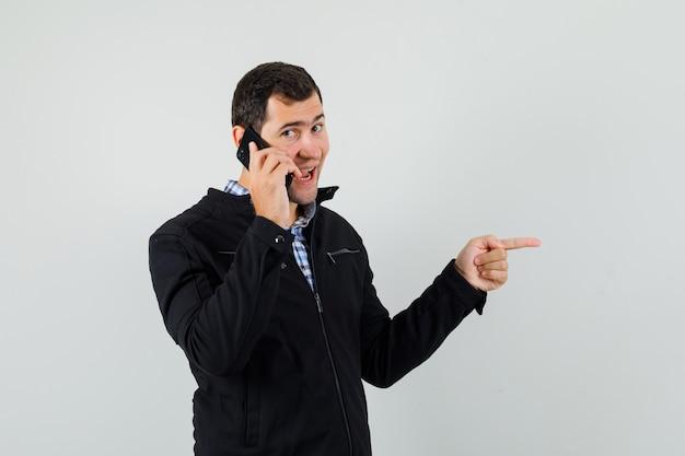 Jonge man praten over de mobiele telefoon, opzij wijzen in shirt, jasje en op zoek gelukkig. vooraanzicht.
