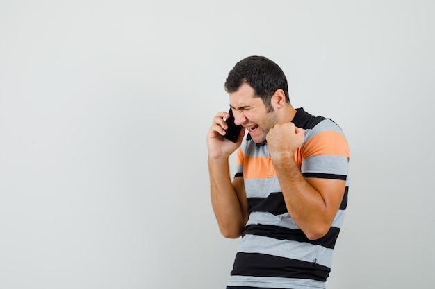 Jonge man praten over de telefoon terwijl winnaar gebaar in t-shirt wordt weergegeven en op zoek gelukkig, vooraanzicht. ruimte voor tekst