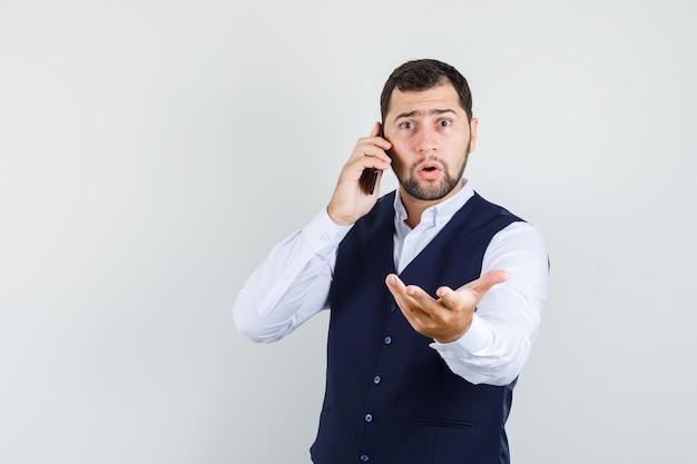 Jonge man praten over mobiel met opgeheven hand in shirt en vest en op zoek verbaasd