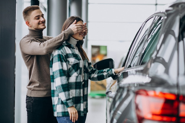 Jonge man presenteert een mcar aan zijn vriendin in een autoshowroom