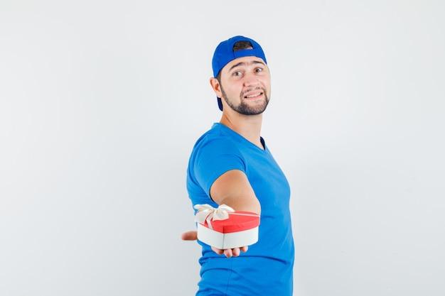 Jonge man presenteert geschenkdoos in blauw t-shirt en pet en kijkt optimistisch