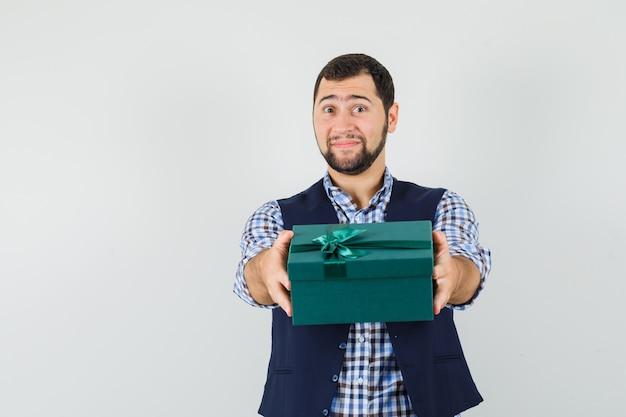Jonge man presenteert geschenkdoos in overhemd, vest en kijkt zacht.