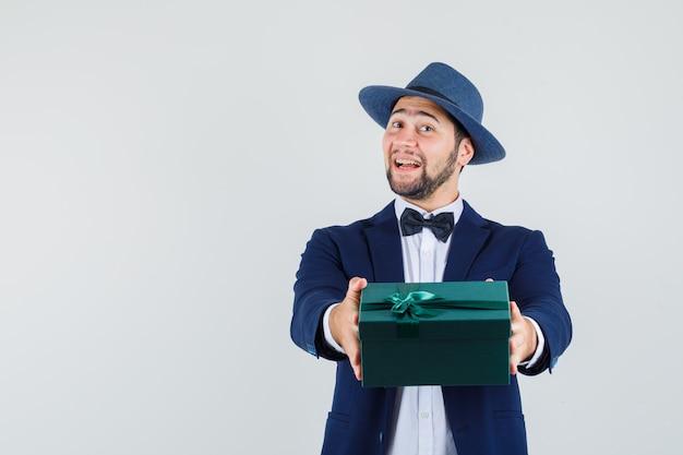 Jonge man presenteert geschenkdoos in pak, hoed en op zoek vrolijk, vooraanzicht.