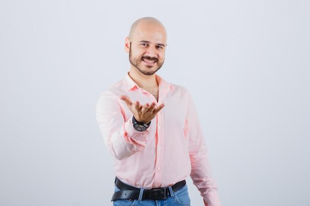 Jonge man presenteert iets in shirt, spijkerbroek en ziet er gelukkig uit, vooraanzicht.