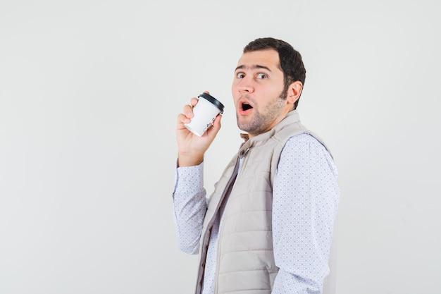 Jonge man probeert afhaalmaaltijden kopje koffie in beige jas te drinken en kijkt verbaasd, vooraanzicht.