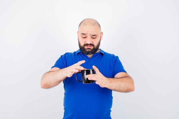 Jonge man probeert een kopje met hete thee in een blauw shirt vast te houden en ziet er verontrust uit, vooraanzicht.