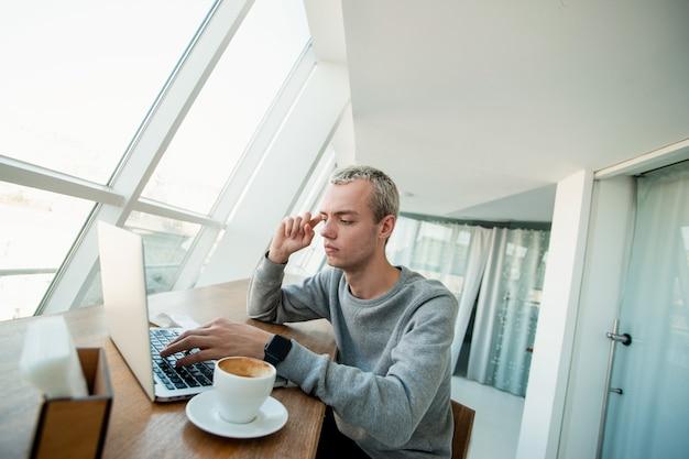 Jonge man probeert probleem op te lossen. geconcentreerde mannelijke programmeur zit voor zijn laptop en masseert zijn slaap met wijsvinger denkend aan werk. freelance-concept.