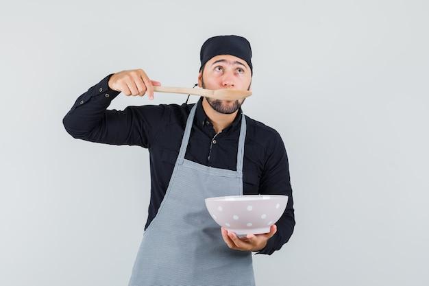 Jonge man proeverij maaltijd met houten lepel in overhemd, schort en aarzelend, vooraanzicht op zoek.