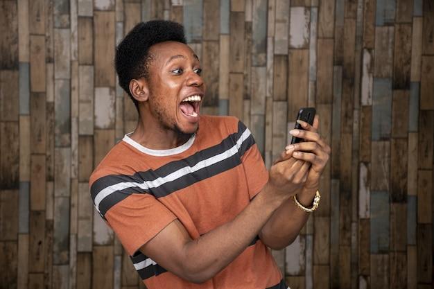 Jonge man raakt opgewonden over zijn telefoon terwijl hij er vrolijk naar schreeuwt