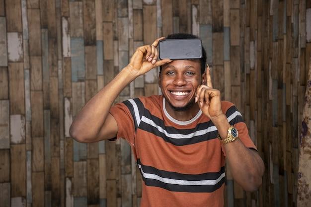 Jonge man raakt opgewonden over zijn telefoon terwijl hij hem tegen zijn hoofd houdt